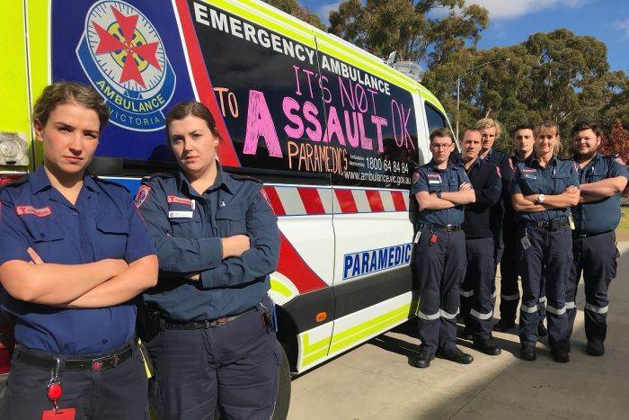 Paramedics standing in front of their vehicle with the words it's not ok to assault paramedics