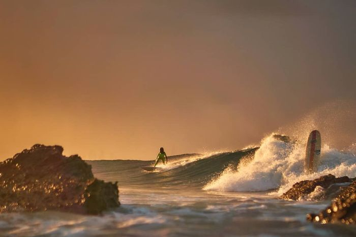 A surfer riding a wave at sunrise.
