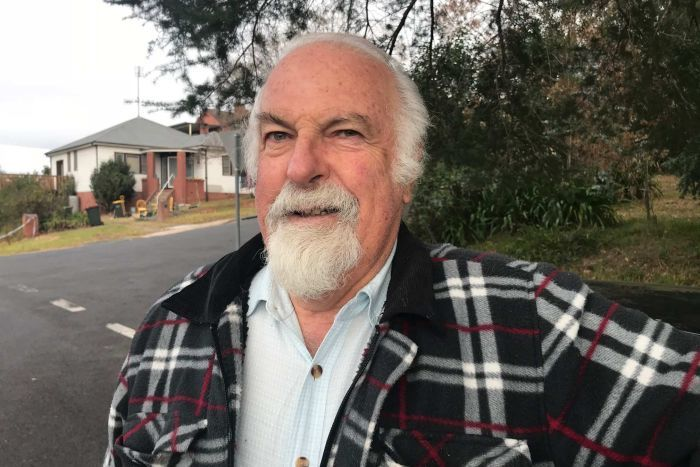 Bob Russell smile while standing on a suburban street.