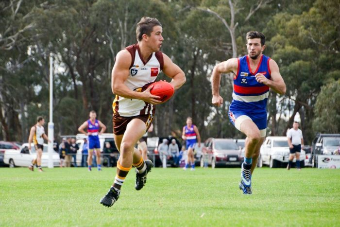 A Huntly footballer prepares to kick as he's chased by a North Bendigo player.