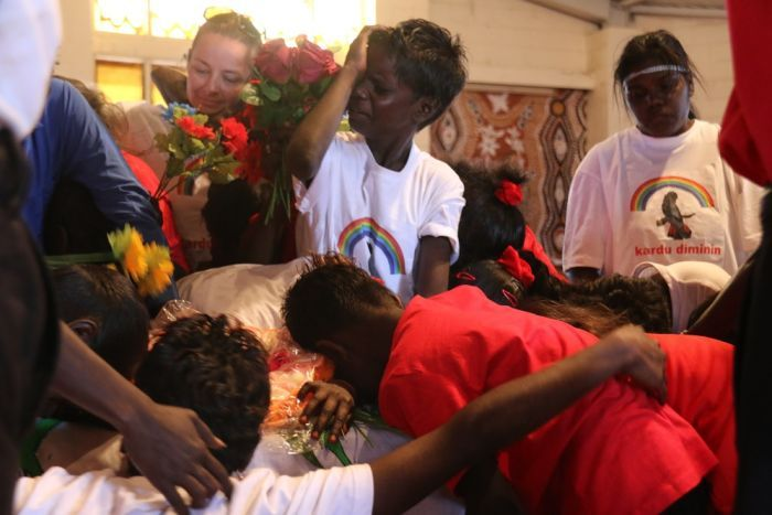 A child wipes tears from his face as others hug the coffin of Mr E Perdjert