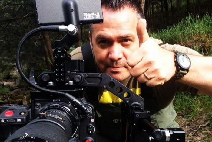 Max Moller in Tasmanian wilderness with camera.