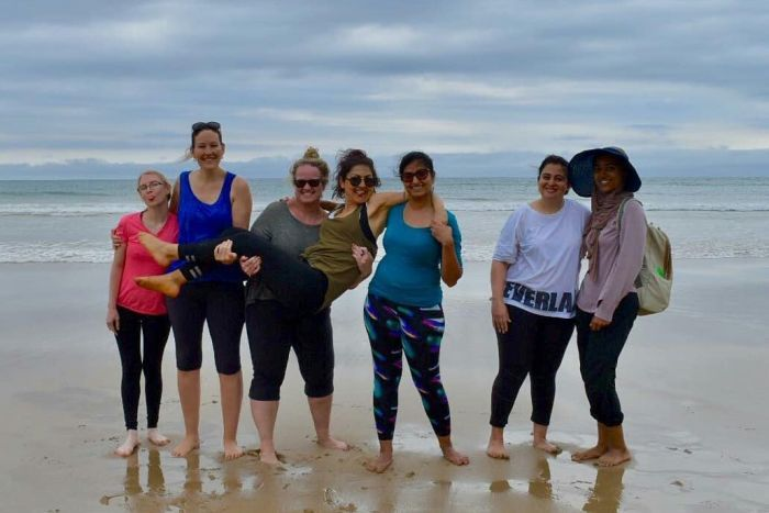 Seven women in exercise clothes stand barefoot on a beach.