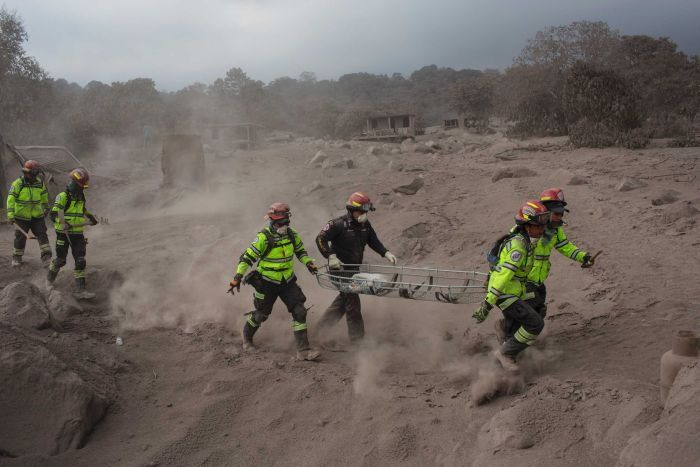Rescue workers run for cover near Volcan de Fuego. The area is covered in piles of thick grey ash.