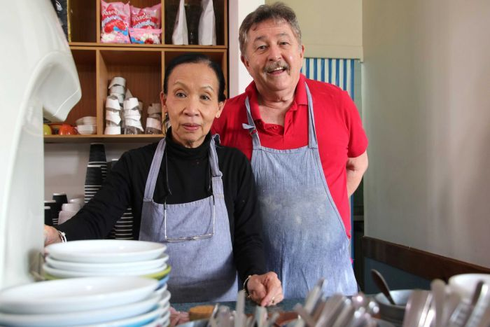 Delphine and Patrick Sullivan wearing aprons inside their cafe, with dishes blurred in the foreground.