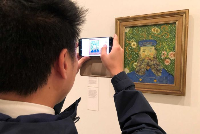 A man takes a photo of a painting on display at the National Gallery of Victoria.