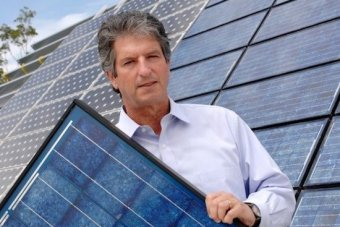 Professor Martin Green standing in front of a solar-panelled roof holding a solar panel