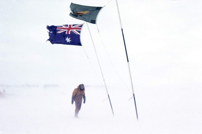 Sydney Kirkby walking in Antarctica, below Australian and boxing kangaroo flags, date unknown.