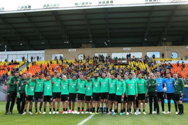 The Socceroos squad links arm with supporters in the background at training
