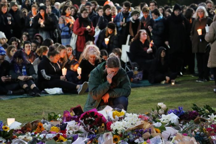 A woman in a coat crouches with her hand on her face, next to a huge pile of flowers, with a crowd holding candles behind her