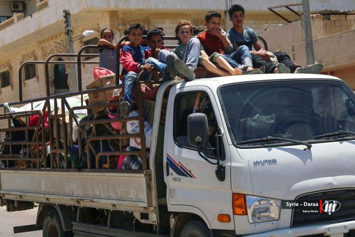 Children sit atop a small truck, crammed with belongings