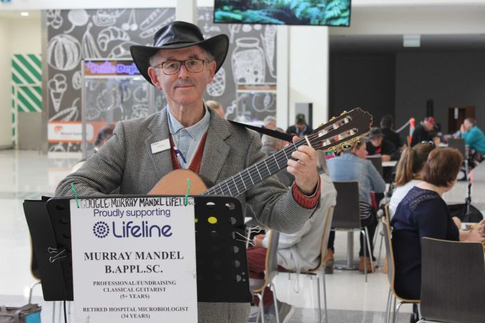 Murray stands behind his music stand holding his guitar in a shopping mall. He is smiling.