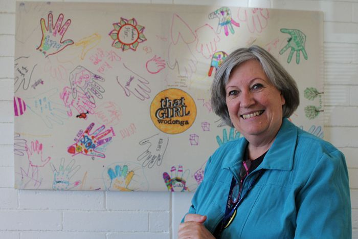 Gateway's Health Tricia Hazeleger stands in front of a mural that has drawings of women's and words of respect on it.