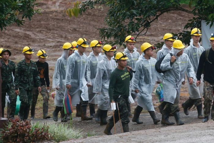 Rescuers walk toward the entrance to a cave complex where five were still trapped.