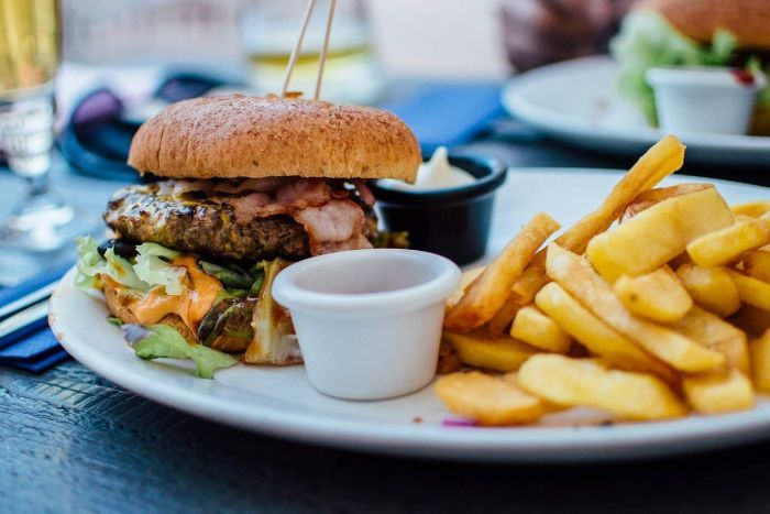 A burger and fries sit on a white plate.