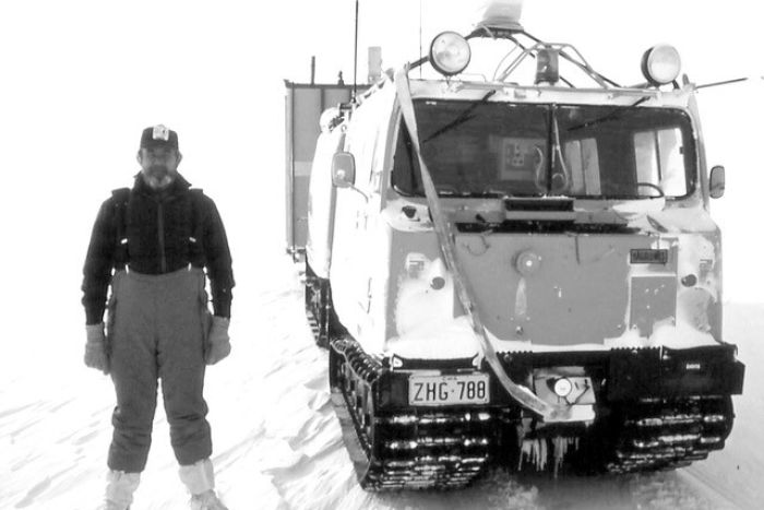 Man standing in snow alongside large vehicle