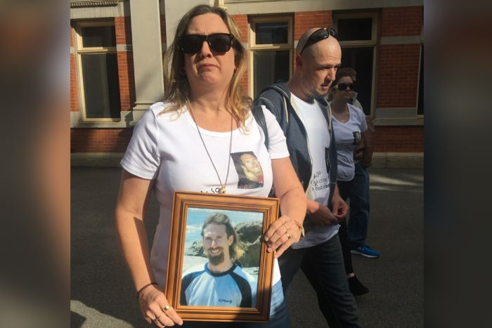Two women and a man hold a photo of a young man outside the Perth Supreme Court.