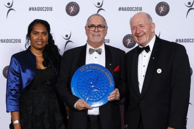 Russell Taylor holds a large, round, blue Naidoc award,standing between a woman and a man, all on a red carpet