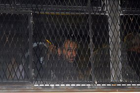An activist arrested aboard a Gaza-bound ship looks out a bus window upon arrival at Ella prison
