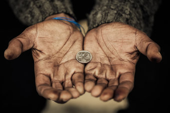 Dirty hands holding out a coin