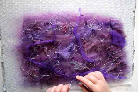 adding viscose, silk, and other felting embellishments to purple wool