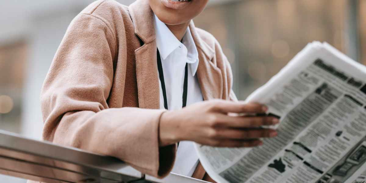 crop cheerful black businesswoman reading newspaper on street