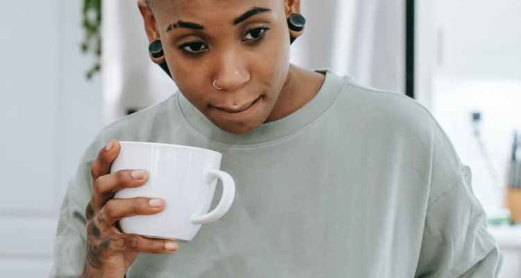 thoughtful young black woman standing in kitchen and drinking coffee