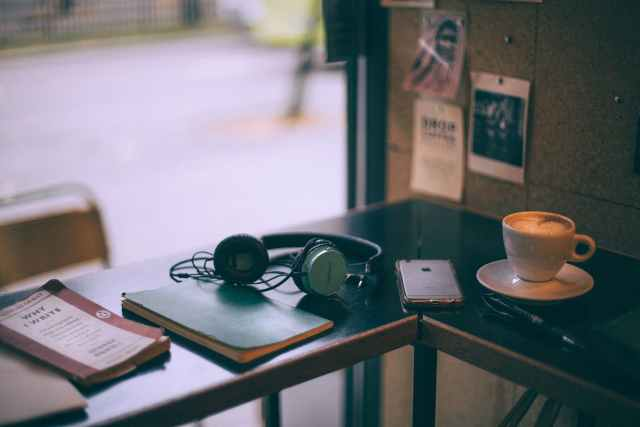 headphones near smartphone and cappuccino on cafe table
