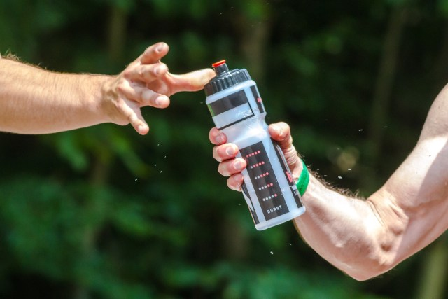 Water bottle being handed to a desperate hand