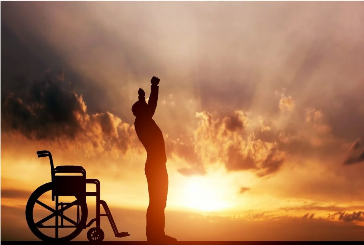 Disabled person standing in front of wheelchair with the sunset in the background