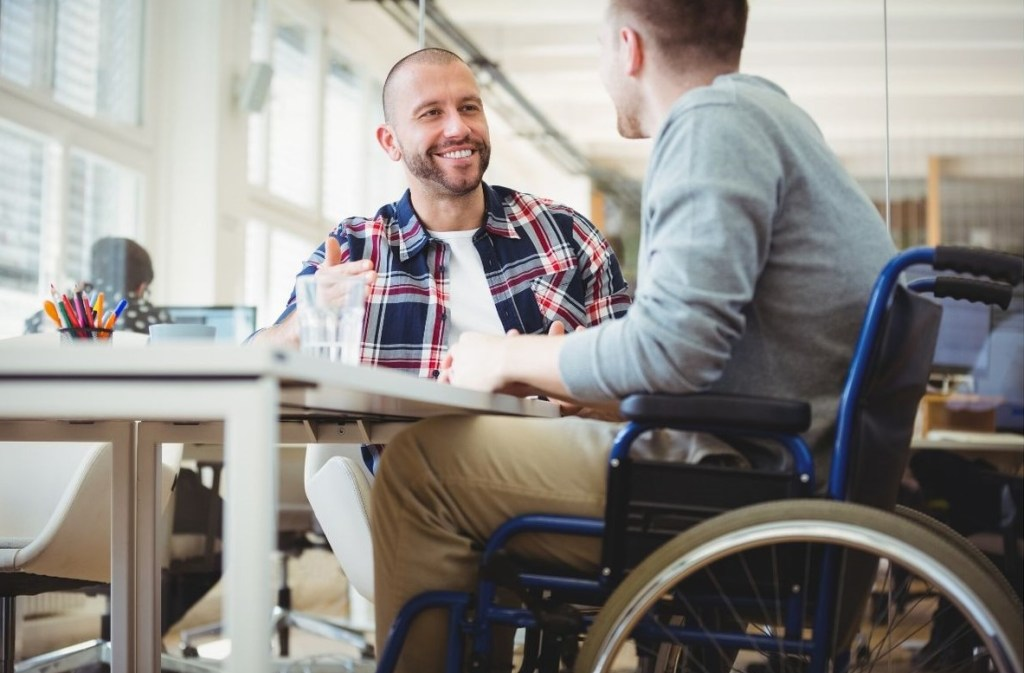 A disabled man in a wheelchair sat at a table with a friend having a chat