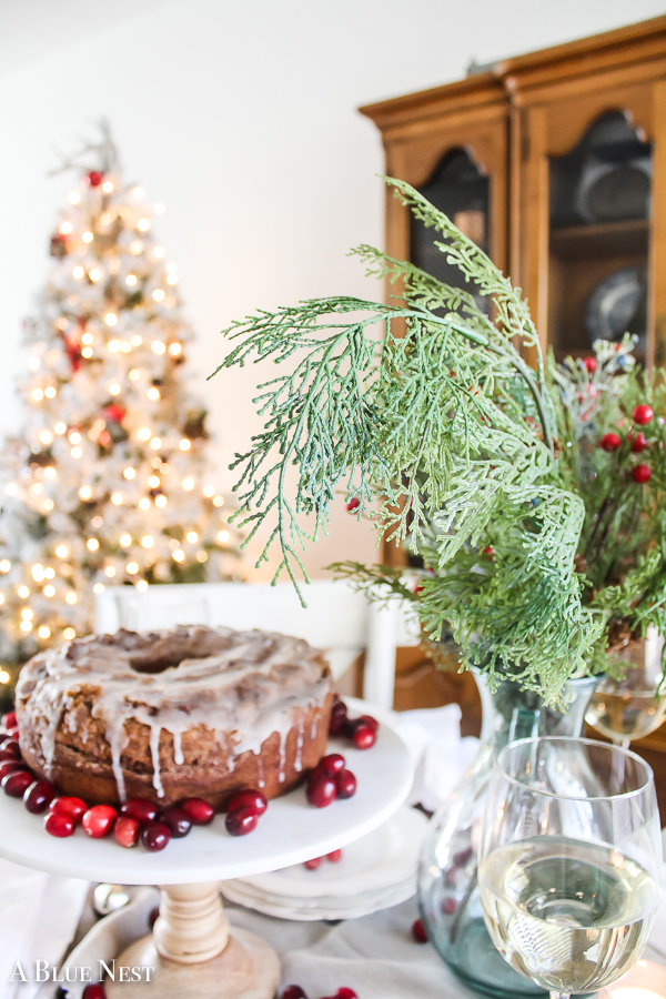 Classic linens and dishes paired with pops of festive colors, yummy treats and faux florals come together to create a casually elegant Christmas tablescape perfect for any event with minimal fuss.