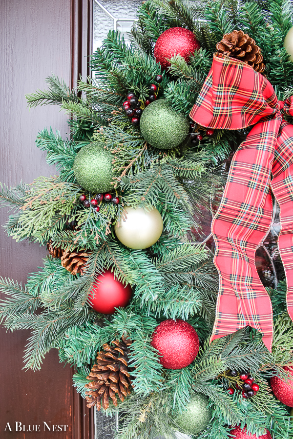 Learn house to transformed any plain evergreen wreath into a classic and whimsical DIY ornament Christmas wreath with a few leftover ornaments and ribbon!