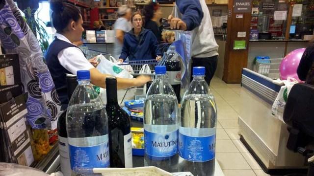Waren werden von der Kassiererin in Plastiktüten verpack