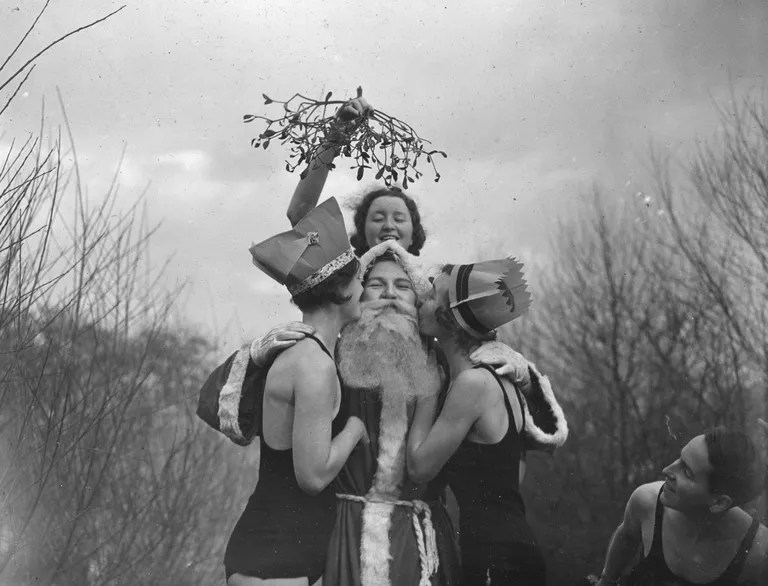 Santa Claus getting a kiss under the mistletoe