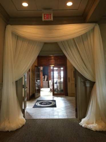 Fabric draping transforms the entrance into a welcoming feel. Design by Above the Rest Event Designs.