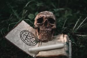 Black magic book with occult symbols and skull