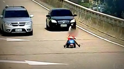 Bimbo, 8 anni, guida un triciclo in un'autostrada in Brasile