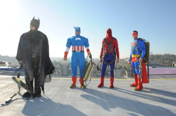 Lavano le finestre di un ospedale pediatrico vestiti da supereroi