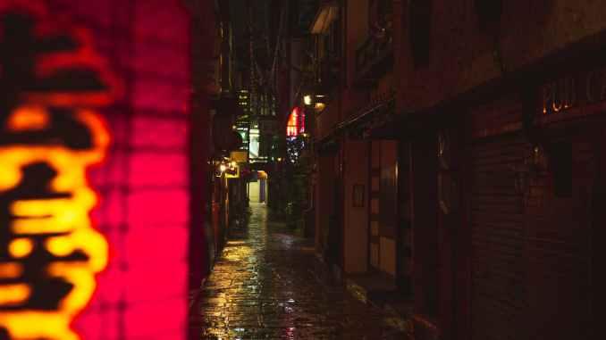 narrow street with wet cobblestone footpath