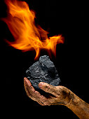 Hand and burning chunk of coal
