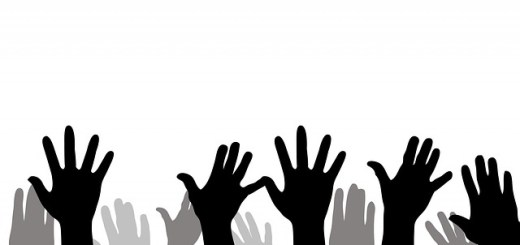 grayscale image of hands raised in the air with open palms