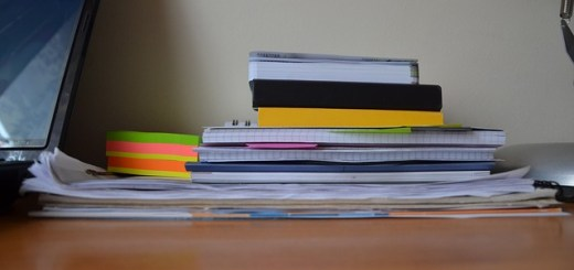 stack of papers and notebooks on a desk