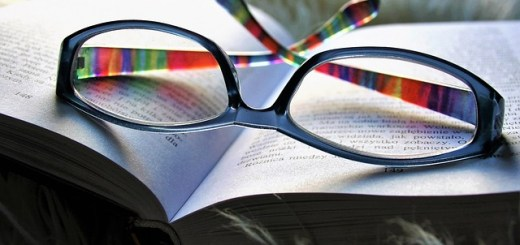 rainbow framed glasses sitting upside down on an open book