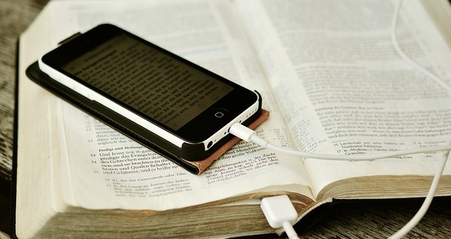 image of open bible, and phone sitting on top with cord to charge it with the plugged in into the bible
