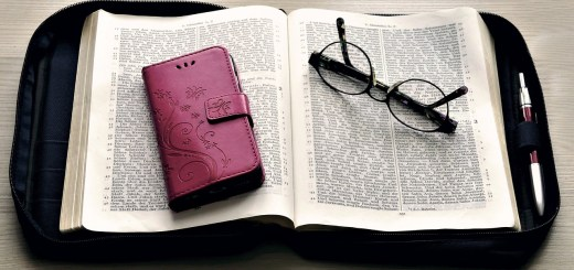 phone in case on top of an open bible with glasses folded sitting on the page