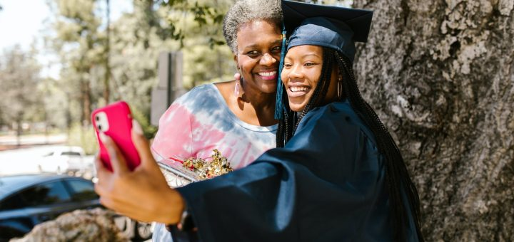 A young black woman taking a selfie with an older black woman. Cap and gown are black, phone being held out is red and there are huge smiles on their faces.