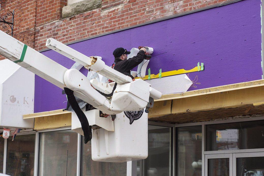 Un ouvrier installe une nouvelle enseigne sur un nouveau café de Charlottetown. - PC/Brian McInnis