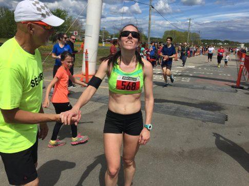 Une Emily Hamilton tout sourire est accueillie par un bénévole du 10 km Chaleur après son triomphe dans la catégorie féminine. - Acadie Nouvelle: Robert Lagacé