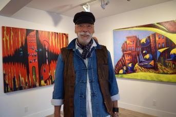 Cecil D Long devant deux toiles exposées à la Galerie Apple Art. - Acadie Nouvelle: Sylvie Mousseau